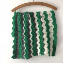 green, cream and grey baby blanket hanging on vintage wood coat hanger against white wall.