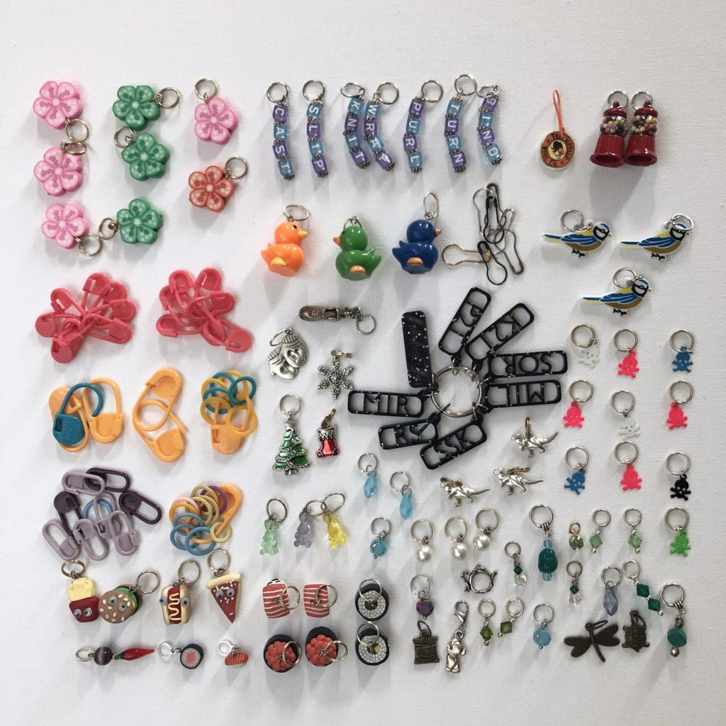 dozens of stitch markers with different designs