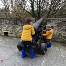 Two children in matching blue rain boots and yellow coats playing pretend with an antique canon.