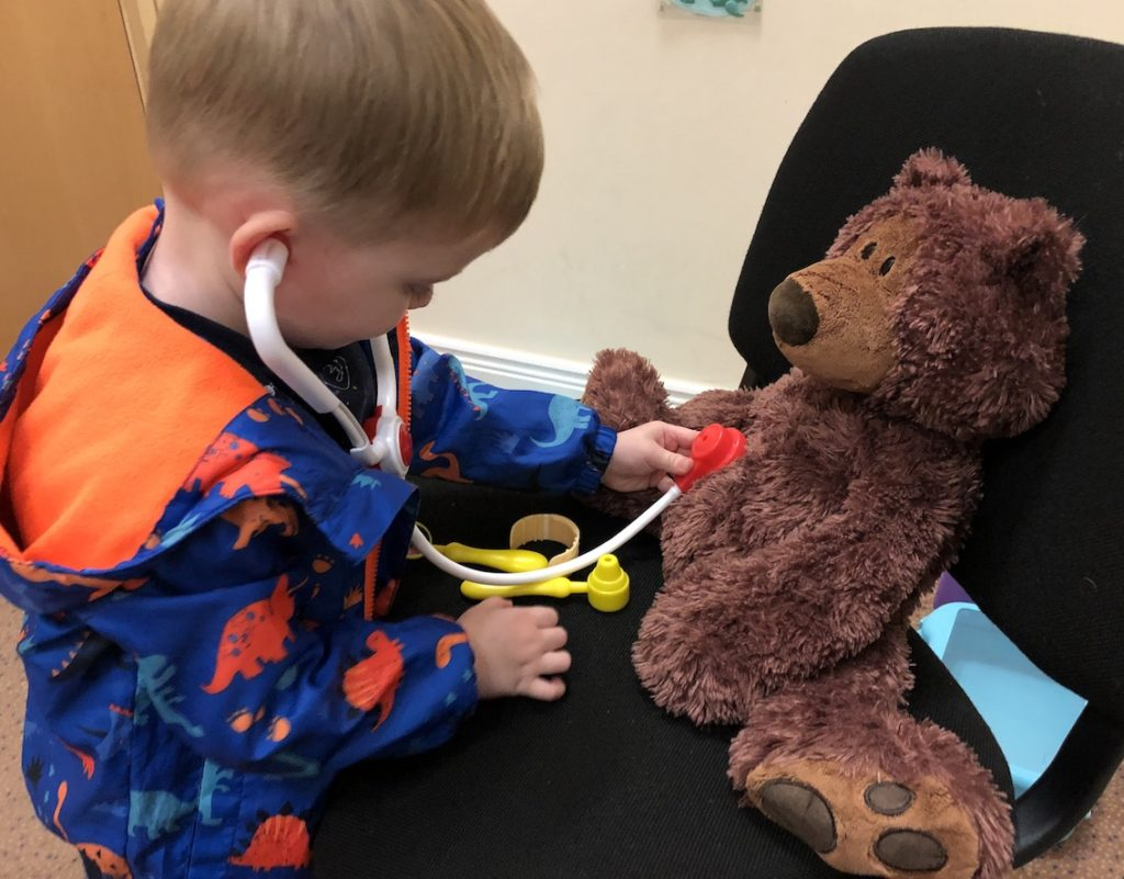 A child using a toy stethoscope to listen to a stuffed animal bear's heartbeat.