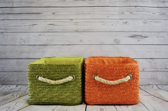 two baskets, one green and one orange, side-by-side against a white shiplap backdrop