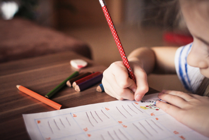 A child's hand is writing with coloured pencils for a chore chart