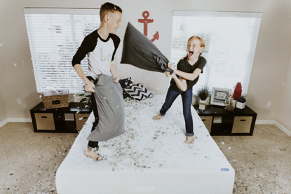 a young boy and young girl, presumably siblings, have a pillow fight while standing atop a bed.