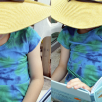 child wearing handmade tie-dye tee and reading a book with a floppy sunhat on.