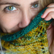Woman with green and amber multicolour eyes looking into camera with hand knit shawl held to her face. The yarn in the shawl matches her eyes.