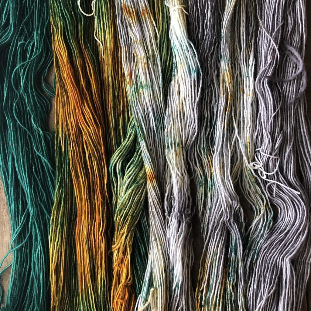 Yarns drying with deep green on the left then rusty colors then off-white.
