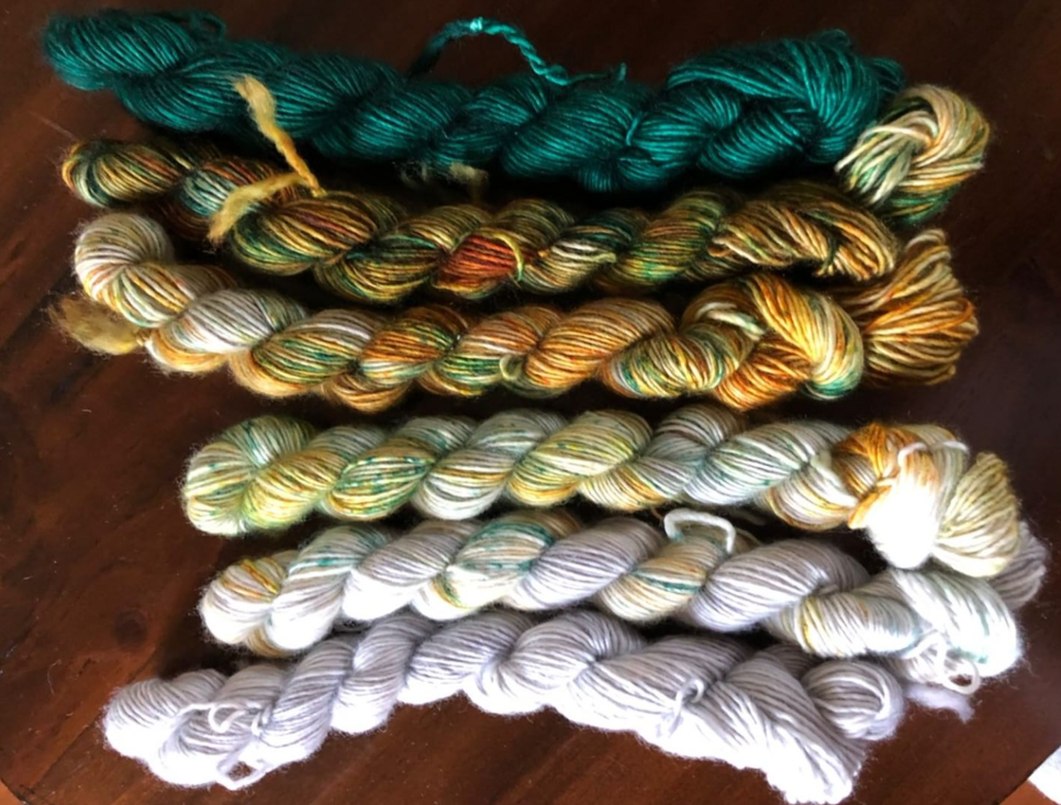 Yarns mini skeins with deep green on the left then rusty colors then off-white.