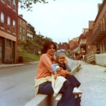 Mother with black hair and peach shirt sitting on the curb holding toddler with train conductor hat.