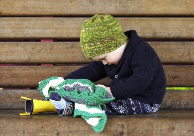 Baby on wood bench taking off rain boots while wearing green hand knit hat
