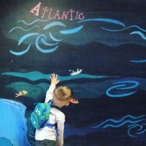 child reaching to touch a mural of the Atlantic ocean
