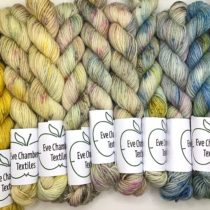 12 Mini Skeins in a rows starting with yellow and fading to greens and then blues. Eve Chambers Textiles label on each skein with an apple logo.